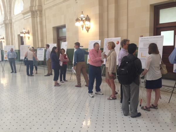 People standing in a room looking at poster boards and talking to each other.