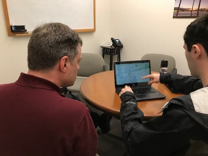 An older man and a younger man are sitting at a desk in a small room. They are looking at a laptop and pointing to the screen. They seem focused.