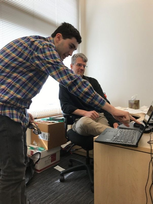 An sitting, older man and a standing, younger man are looking at a computer perched on the edge of a desk. The younger man is hunched and pointing at the computer while the older man looks on.